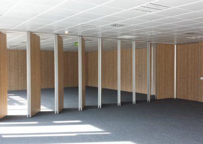 Sala Multiusos, paneles móviles en madera, puertas, cabinas sanitarias.